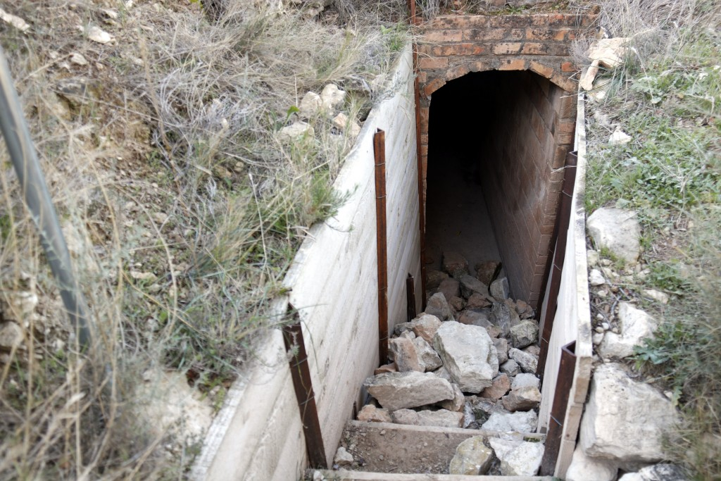 Pla obert on es poden veure un munt de pedres obstaculitzant l'entrada a un dels refugis de les trinxeres de Montgai, el 4 de gener de 2018. (Horitzontal)
