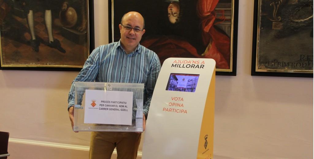 Imatge de l'alcalde de Cervera, Ramon Royes, sostenint una urna, al costat del dispositiu tàctil instal·lat al vestíbul de la Paeria perquè els veïns puguin presentar les seves propostes, el 24 de gener del 2019. (Horitzontal)