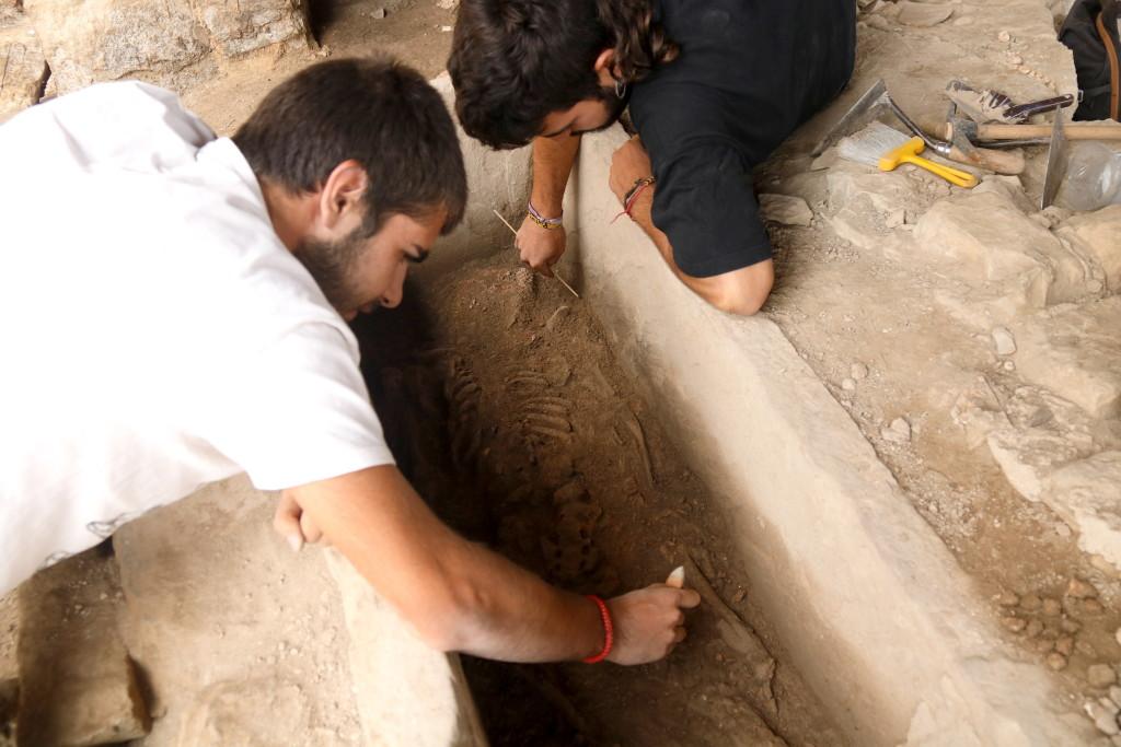 Pla mitjà on es poden veure dos arqueòlegs netejant les restes del cos de l'època tardo-romana que s'ha localitzat a la Iesso de Guissona, el 17 de juliol de 2019. (Hortizontal)