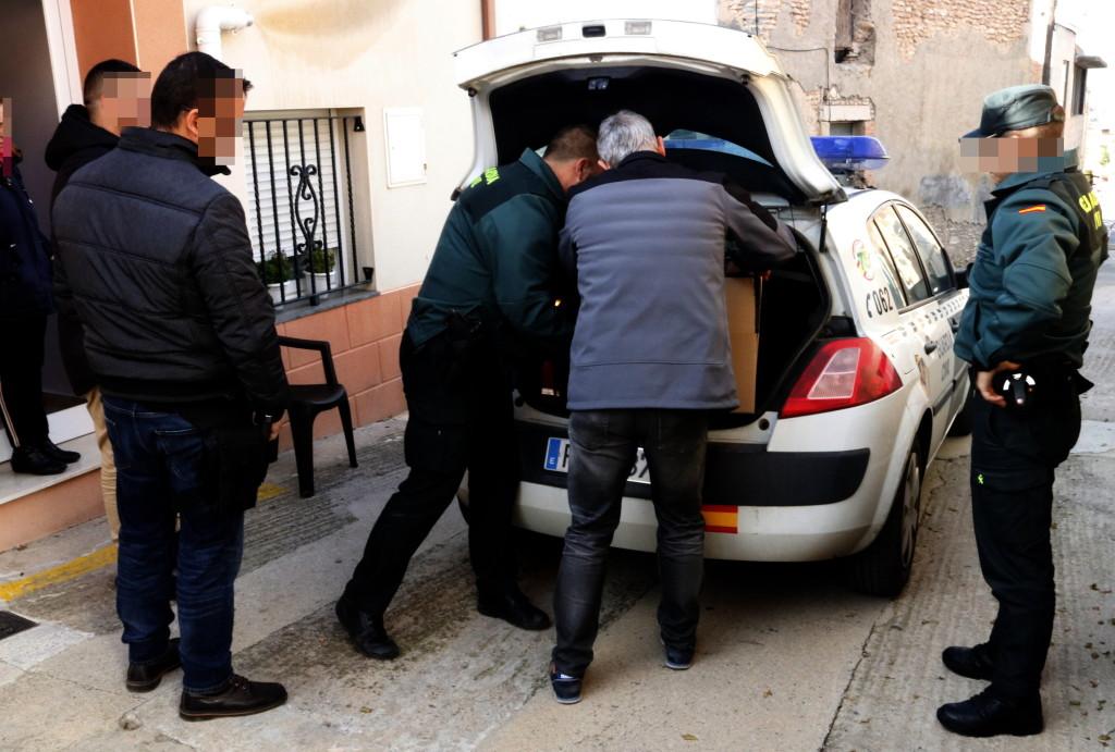 Pla mitjà on es poden veure agents de la Guàrdia Civil amb un dels detinguts a l'operació antidroga a Bellpuig i carregant cotxes al vehicle policial, el 20 de novembre de 2019. (Horitzontal)